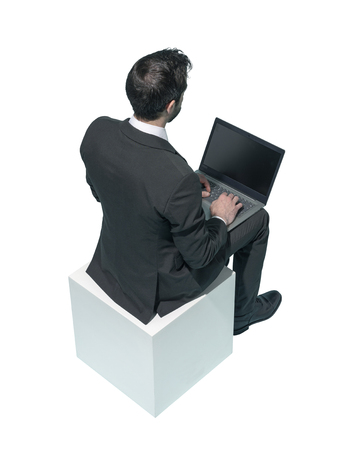 Corporate businessman sitting and working with his laptop on white background Standard-Bild - 124477657