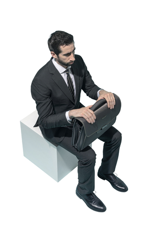 Corporate businessman sitting and waiting on white background Standard-Bild - 124477658