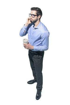 Man having a coffee break and talking on the phone, white background Standard-Bild - 124477823