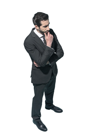 Confident businessman posing with hand on chin, white background Standard-Bild - 124477963