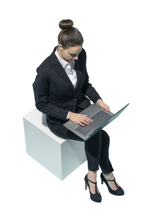 Corporate businesswoman sitting and using a laptop on white background Standard-Bild - 124477965