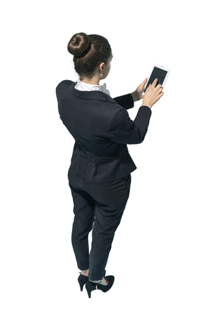 Professional corporate businesswoman using a digital tablet on white background Standard-Bild - 124478056
