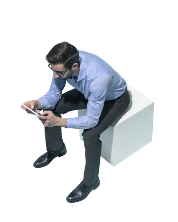Man sitting and using apps on a digital tablet, white background Standard-Bild - 124478058