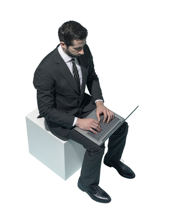 Corporate businessman sitting and working with his laptop on white background Standard-Bild - 124478270