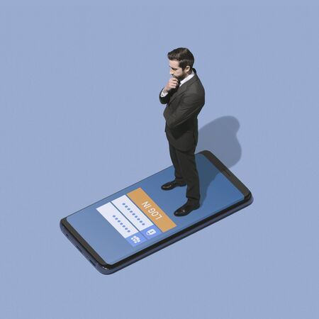 Pensive businessman standing on a smartphone and logging in into a mobile app profile