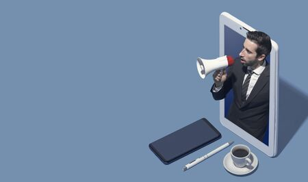 Business executive in a smartphone shouting out with a megaphone, marketing and technology concept