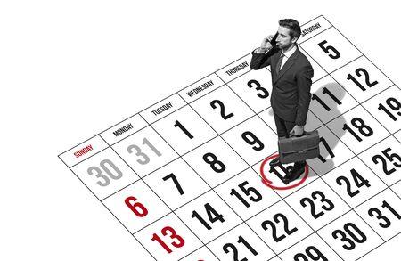 Homme d'affaires planifiant des rendez-vous au téléphone, il se tient sur un calendrier de planification