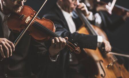 Profesjonalna orkiestra smyczkowa symfoniczna występująca na scenie i grająca koncert muzyki klasycznej, na pierwszym planie skrzypek