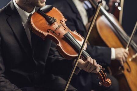 Orquesta de cuerdas sinfónica profesional actuando en el escenario y tocando un concierto de música clásica, violinista en primer plano