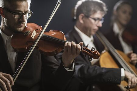 Professional symphonic orchestra performing on stage and playing a classical music concert, violinist playing in the foreground, arts and entertainment concept Фото со стока