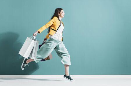 Alegre mujer feliz disfrutando de las compras: lleva bolsas de la compra y corre para obtener las últimas ofertas en el centro comercial Foto de archivo