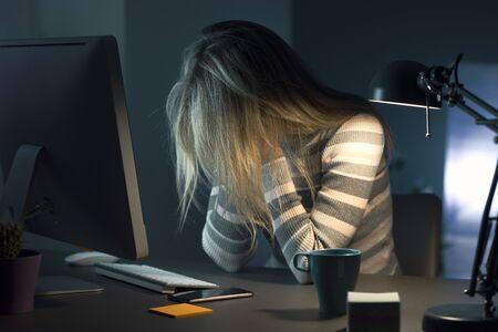 Jeune femme épuisée souffrant de maux de tête faisant des heures supplémentaires tard dans la nuit, elle est assise au bureau, la tête dans les mains