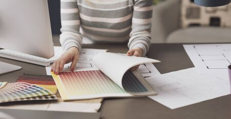 Professional creative interior designer searching swatches in a book and browsing pages