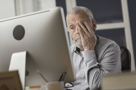 Confused senior citizen using a computer, he is staring at the screen and feeling tired and clueless, technology and elderly concept