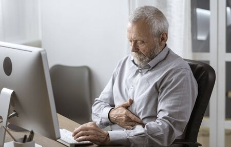 Senior man working in the office and having a bad stomach pain, elderly and health concept