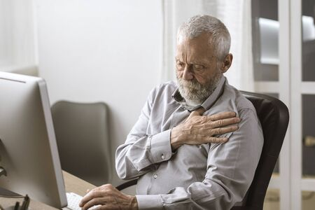 Concerned senior man having an heart attack, he is sitting at desk and touching his chest Banque d'images