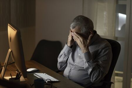 Lonely sad senior man connecting at night with his computer: he is having an headache, feeling sad and lonely, technology and elderly concept Stock Photo