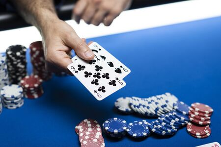 Man playing Texas Hold 'em poker at Casino, he is holding two cards