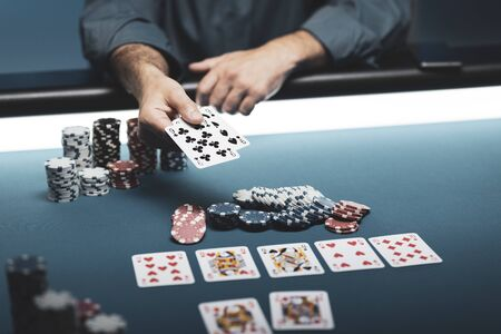 Man playing Texas Hold em poker at Casino, he is holding two cards 写真素材