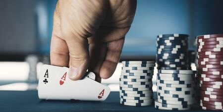 Hold em Texas poker tournament at casino: a man is holding two ace cards 写真素材