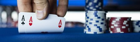 Hold em Texas poker tournament at casino: a player is holding two ace cards 写真素材