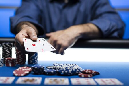 Hold 'em Texas poker tournament at casino: a man is holding two ace cards