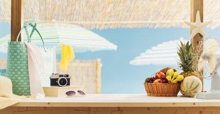 Fruta fresca, bolsas y cámara en el quiosco del bar de la playa, concepto de verano y turismo