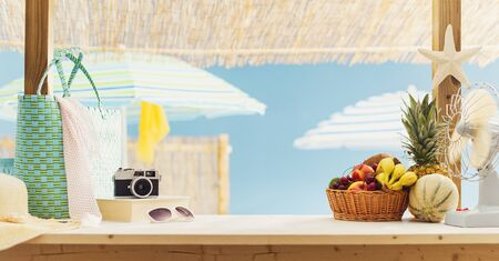 Fresh fruit, bags and camera on the beach bar kiosk, summer and tourism concept