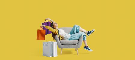 Cheerful happy shopaholic woman with lots of shopping bags, she is sitting on an armchair and celebrating, blank copy space