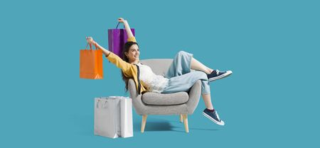 Donna allegra e felice dello shopping con un sacco di borse della spesa, è seduta su una poltrona e festeggia con le braccia alzate