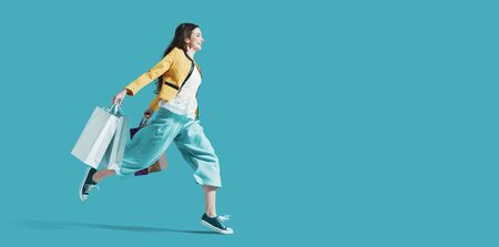 Alegre mujer feliz disfrutando de las compras: lleva bolsas de la compra y corre para obtener las últimas ofertas en el centro comercial