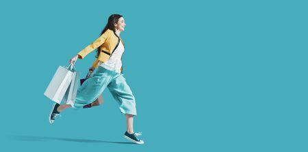 Joyeuse femme heureuse faisant du shopping : elle porte des sacs de courses et court pour obtenir les dernières offres du centre commercial