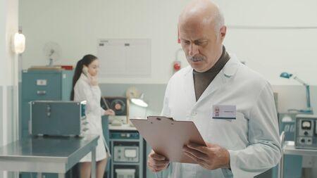 Scientifique principal travaillant dans un laboratoire de style vintage avec des machines rétro, il vérifie les informations sur un presse-papiers