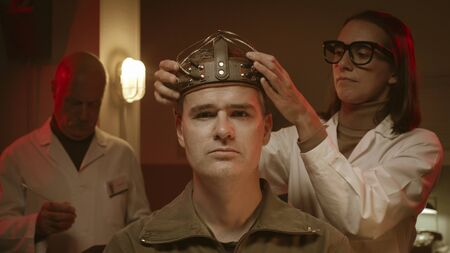 Scientists making experiments on a human brain in a vintage style lab, a man is wearing a sci-fi helmet and researchers are testing him