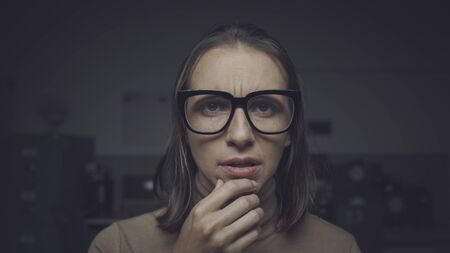 Puzzled woman staring at the camera and thinking with hand on chin