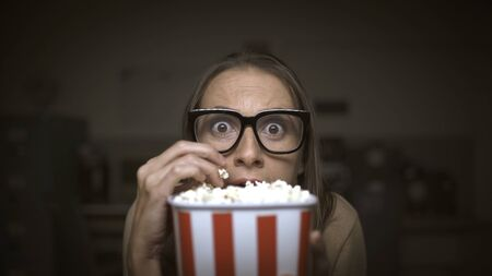 Funny scared woman watching horror movies and eating popcorn at home