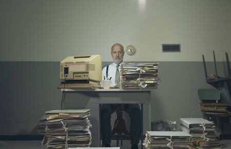 Frustrated vintage style businessman working in a rundown old office space, he is overloaded with papework Stock Photo