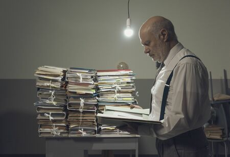 Serious pensive businessman checking a file in a vintage style office and piles of paperwork, business and administration concept Фото со стока