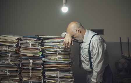 Desperate businessman with lots of paperwork in his messy office at night, he is leaning on a pile of files, bureaucracy and deadlines concept Imagens