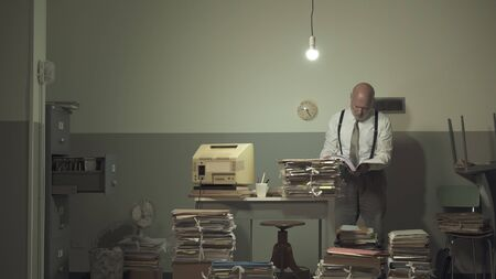 Businessman working in a messy rundown office space, he is surrounded by piles of paperwork and searching for a file