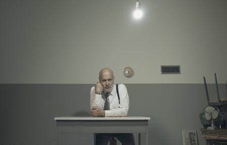 Triste uomo d'affari frustrato che lavora in un ufficio disordinato, è seduto a una piccola scrivania e si appoggia al braccio