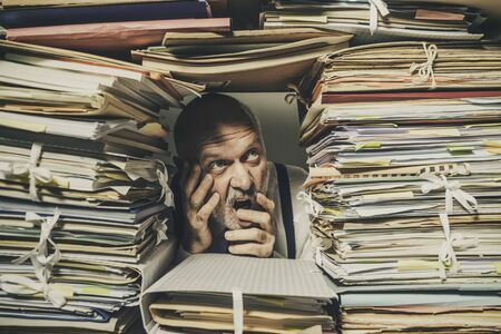 Panicked stressed businessman overwhelmed with paperwork, taxes and accounting concept