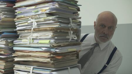 Stressed frustrated business executive sitting at desk and peeking behind a pile of paperwork Imagens