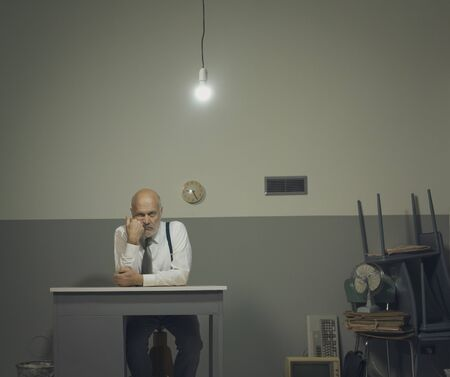 Sad frustrated business executive working in a cluttered office, he is sitting at a small desk and leaning on his arm