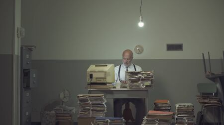 Frustrated vintage style businessman working in a rundown old office, he is overloaded with papework Stok Fotoğraf - 133006383