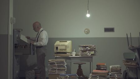 Corporate businessman searching for files in a rundown messy office with old computer and piles of paperwork