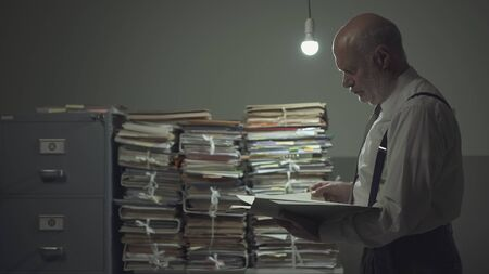 Serious pensive businessman checking a file in a vintage style office and piles of paperwork, business and administration concept