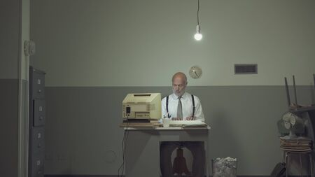 Sad vintage style businessman working in a small rundown office with an outdated computer, he feels frustrated and disappointed Stok Fotoğraf - 133007615