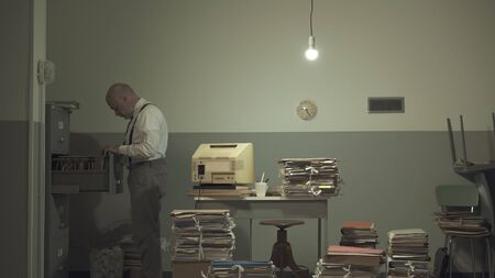 Corporate businessman searching for files in a rundown messy office with outdated computer and piles of paperwork