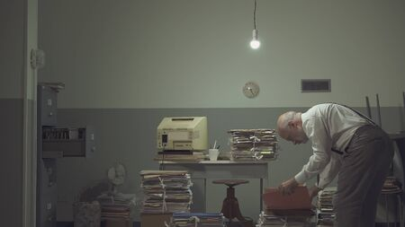 Businessman working in a messy office, he is surrounded by piles of paperwork and searching for a file